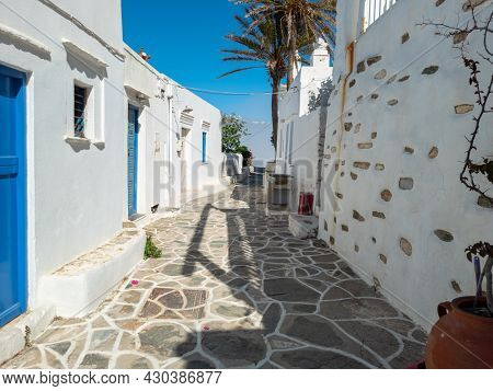 Typical Cyclades architecture on way to Kastro village Sifnos island Greece. Whitewashed stonewall houses blue doors empty cobblestone narrow street under clear sky background. Summer destination.