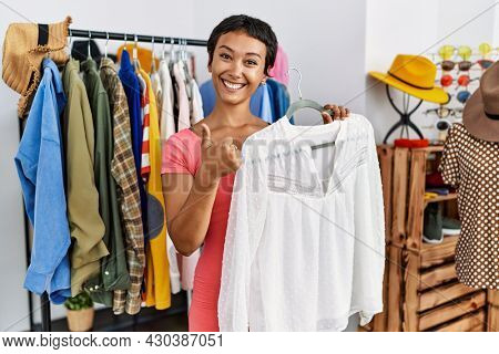 Young hispanic woman with short hair shopping at retail boutique smiling happy and positive, thumb up doing excellent and approval sign