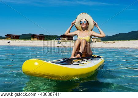 Happy Travel Woman In Straw Hat And Sunglasses Smiling Sitting On Sup Surfboard Sunbathing