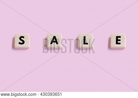 Wooden Cubes With The Inscription Sale On Pink Background
