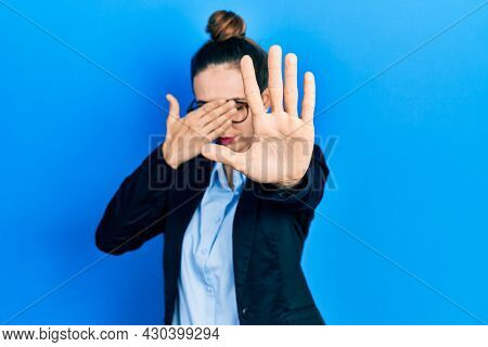 Young hispanic girl wearing business clothes and glasses covering eyes with hands and doing stop gesture with sad and fear expression. embarrassed and negative concept.