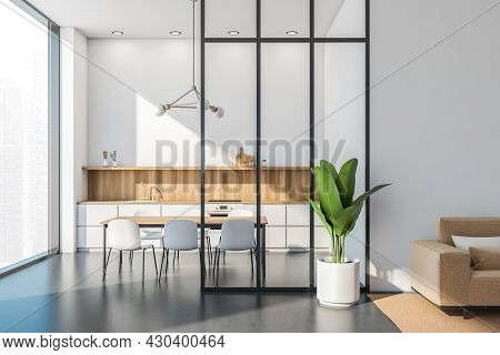 Panoramic White Kitchen Interior With A Simplified Cabinet, Table, Frame Chandelier, Glass Partition