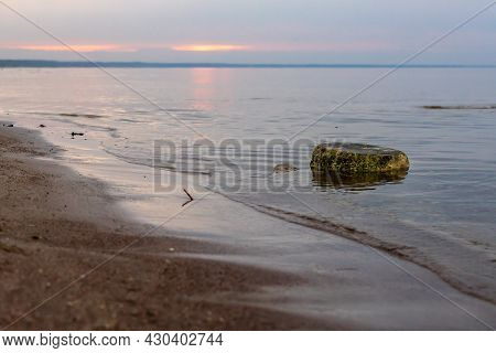 Mossy Rock During Sunset At Klapkalnciems Beach, Latvia After Rainy Day. Dark Sunset Reflecting In C