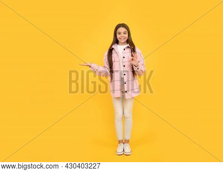 Tween Child In Plaid Shirt Presenting Product. Advertisement. Beauty And Fashion. Latest Trend.