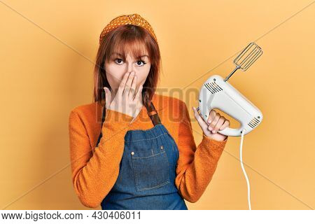 Redhead young woman holding pastry blender electric mixer covering mouth with hand, shocked and afraid for mistake. surprised expression