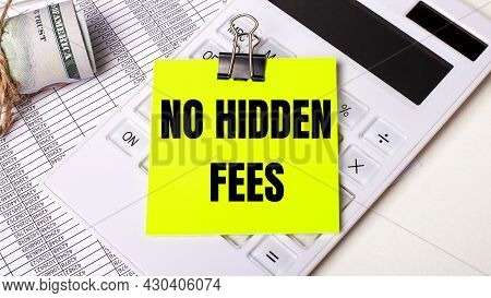On A Light Background - Cash, A White Calculator And A Yellow Sticker Under A Black Paper Clip With