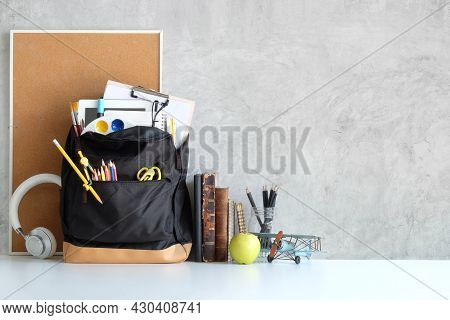 Backpack With School Stationary And Headphone On White Table. Back To School Concept.
