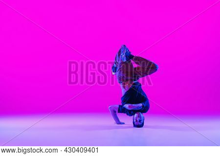 Portrait Of Young Man, Break-dance Dancer Dancing Solo In Modern Clothes Isolated Over Bright Magent