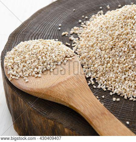 Raw Dried Broken Barley Cereal Grain Texture Background Macro Closeup. Barley Groats, Coarse Barley