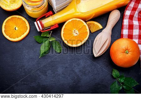 Freshly squeezed orange juice in glass bottle with straw. Fruity still life on black backdrop and grey concrete surface rustic style.