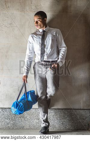Dressing In White Shirt, A Black Tie And Gray Pants, Carrying A Blue Bag, A Young Handsome Black Bus