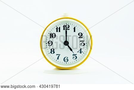 Alarm Clock Yellow Shows The Time 17 O'clock On A White Isolated Background