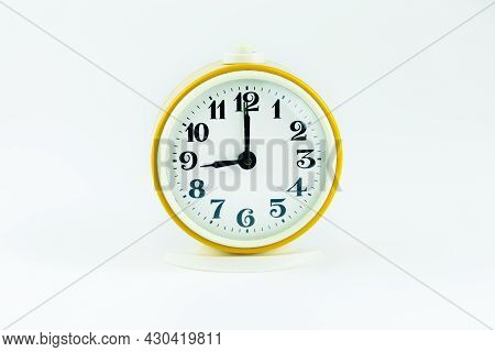 Alarm Clock Yellow Shows The Time 9 O'clock On A White Isolated Background