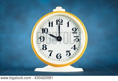 Yellow Alarm Clock Shows Time 22 O'clock On Turquoise Isolated Background
