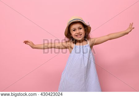 Beautiful Caucasian Ethnicity 4 Years Baby Girl In Summer Blue Dress And Straw Hat, Smiles Looking A