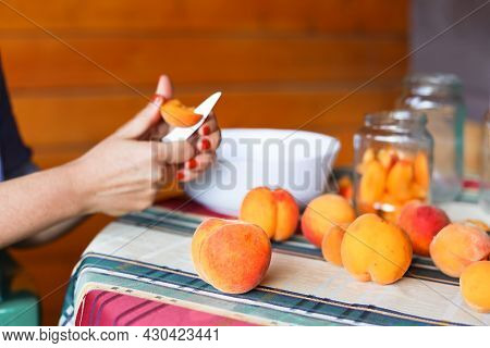 Female Hands Cutting Fresh Sweet Peaches To Make Peach Jam. A Woman Is Sitting On A Wooden Terrace.