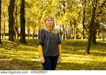 Defocus Blond 40s Woman Standing In Yellow Autumn Park. Happy Beautiful Lady. Women Wearing Grey Pul