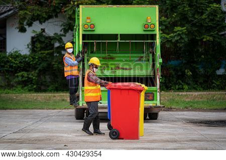 Workers In The Street Are Loading A Garbage Truck,garbage Bin Collection,waste Collector With Rubbis