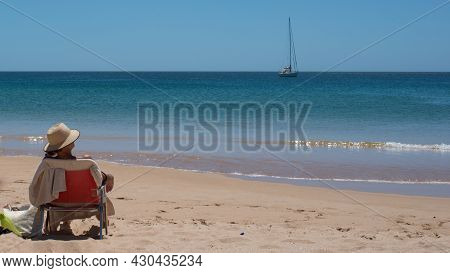 Woman Sitting On A Chair With A Hat, On The Beach And Looking To The Horizon. Photo Taken From Her B