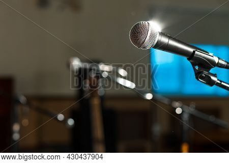 Microphone Illuminated From Behind By A Lantern Illuminating The Stage, Empty Stage Before The Conce