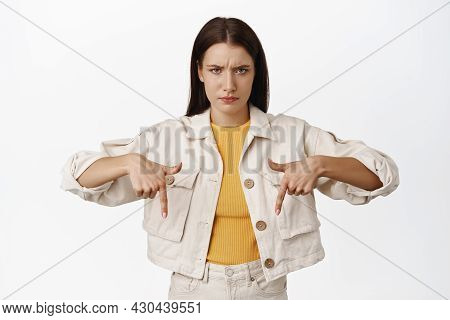 Disappointed Woman Furrow Eyebrows, Pointing Fingers Down And Looking Upset, Complain At Unfair Thin