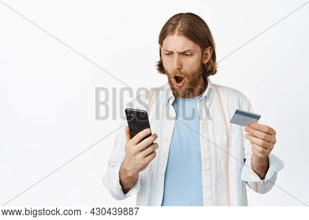 Image Of Blond Man Looks Shocked At His Phone Screen, Bank Account, Gasping Worried, Holding Credit