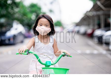 Child Girl Wearing Cloth Face Mask Driving Green Bicycle At Outdoors. Preventing Spread Coronavirus