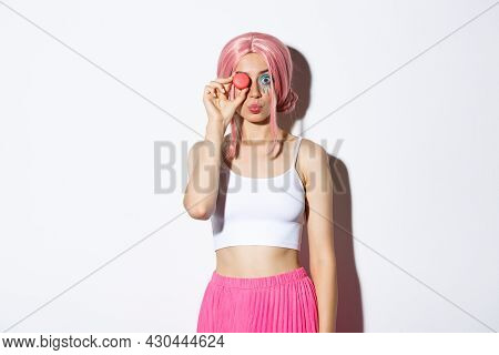 Portrait Of Lovely Girl In Pink Wig, Dressed Up For Party Or Holiday Celebration, Holding Delicious