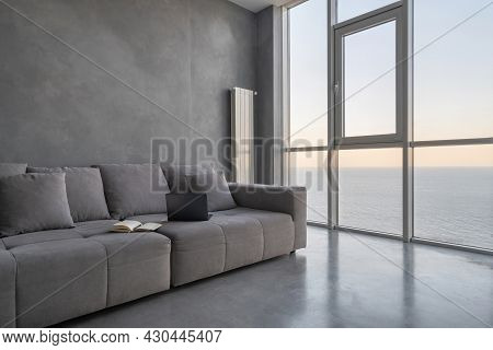 Modern Laptop And Open Planner On Grey Couch In Hotel Room. Cozy Apartment With Loft Style Interior