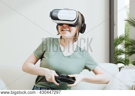 Excited Attractive Woman Gaming With Virtual Reality Headset Or Goggles And Sitting On The Couch, Ho