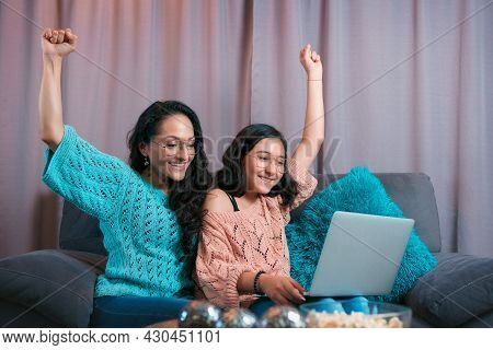 Mom And Daughter Watching A Laptop Sitting On The Sofa At Home, The Two Make Expressions When Lookin