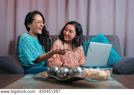 Horizontal view of a mother and her daughter using a laptop, the mother laughs at something she saw on the computer and her daughter turns to see what her mother is doing