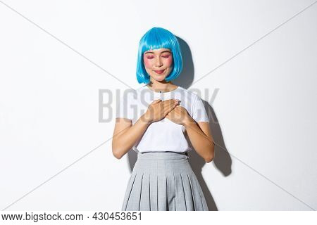 Portrait Of Lovely Asian Girl In Blue Stylish Wig, Close Eyes And Smiling While Holding Hands On Hea