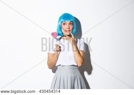 Image Of Silly Asian Girl In Blue Wig, Dressed-up For Halloween Party, Looking Thoughtful, Holding H
