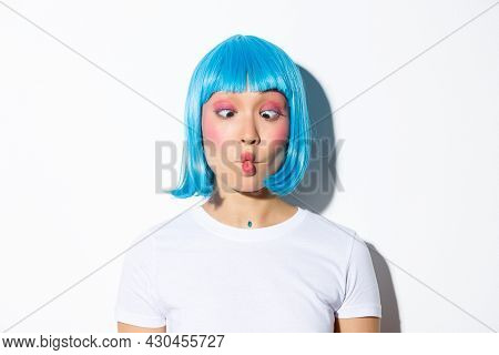 Close-up Of Funny And Silly Asian Girl Entertainer Celebrating Halloween, Wearing Blue Wig, Showing