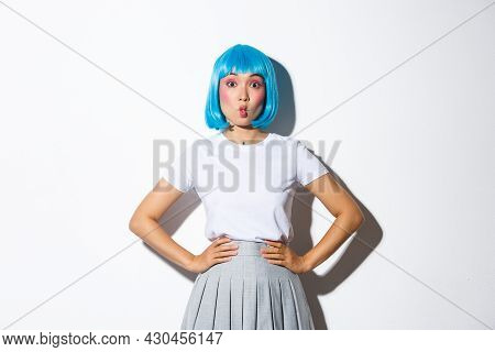 Silly Asian Girl In Blue Party Wig, Grimacing, Making Funny Faces, Wearing Outfit For Halloween Or C