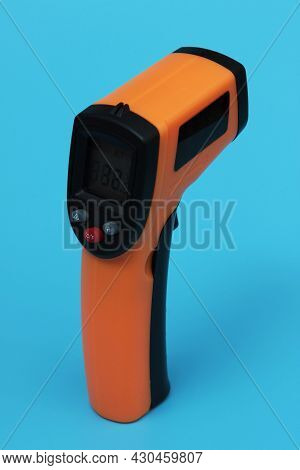 Infrared Thermometer (thermometer Gun) For Measuring Temperature Over Blue Background. Covid-19 Spre