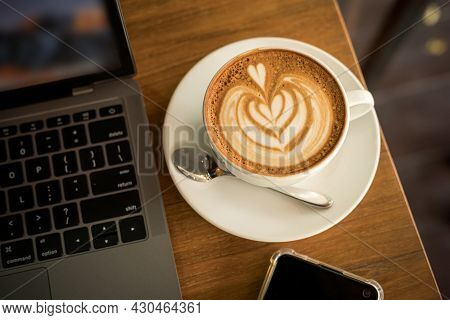 Close-up Of Hot Coffee Latte With Latte Art Milk Foam In Cup Mug And Laptop Computer And Smartphone