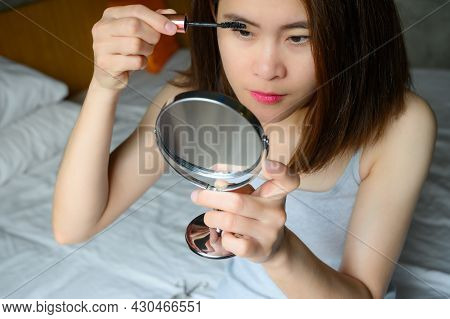Portrait Of Young Asian Woman Applying Black Mascara On Her Eyelashes With A Wand Applicator. Mascar