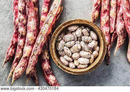 Cranberry beans. Borlotti beans in bowl. Beans pods. Top view.