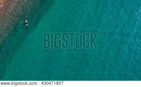 Aerial View From Flying Drone Of Blue Ocean Water With Unrecognized People In The Sea. Paphos Cyprus