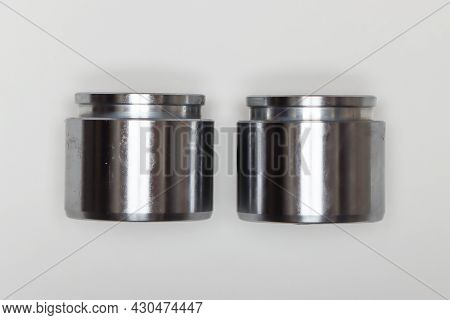 Two Metal Identical Pistons, Parts For Car Repair. A Set Of Spare Parts For Servicing The Braking Sy