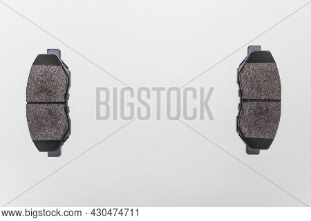 Two Brake Pads On The Edges Of The Table, Parts For Car Repair. A Set Of Spare Parts For Servicing T