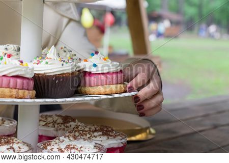 Concept Of Catering And A Sweet Table For A Children's Party. Children's Picnic With Cakes And Sweet