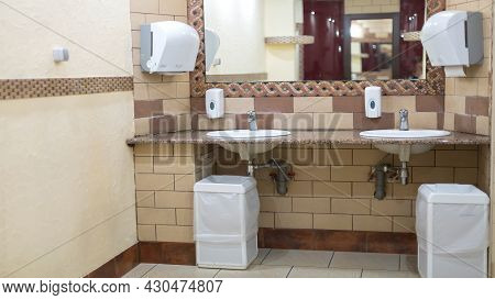 Toilet Room With Washbasins And Mirrors In A Restaurant Or Business Center. Hygiene Standards Of A P
