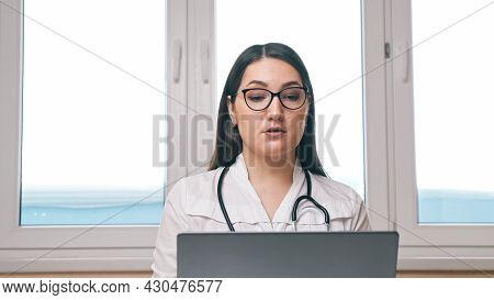 Young Woman Doctor With Glasses And Stethoscope Consults Patient Via Videocall On Laptop Near Window