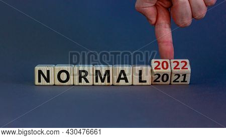 Symbol Of Covid-19 Normal In 2022. Doctor Turns Wooden Cubes And Changes Words 'normal 2021' To 'nor