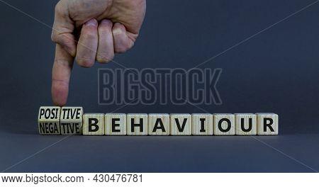 Positive Or Negative Behaviour Symbol. Businessman Turns Cubes, Changes Words Negative Behaviour To
