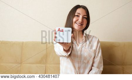 Young Woman Demonstrates Cards With Letters Of The English Alphabet And Pronounce Sounds And Words.