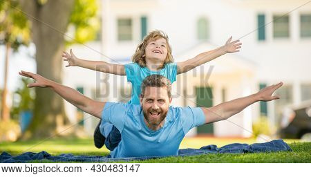 Parent Relax With Small Child Boy On Grass. Dad With Kid On Summer Day. Parenting